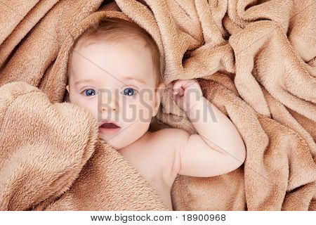 little caucasian baby covered with brown towel