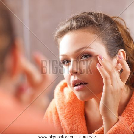 beautiful female with clean skin applying cream in bath