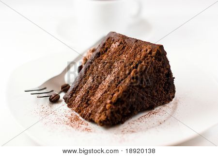 Chocolate cake and a cup of coffee in the background