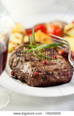 Grilled steak with fresh rosemary and peppercorns served with grilled vegetables