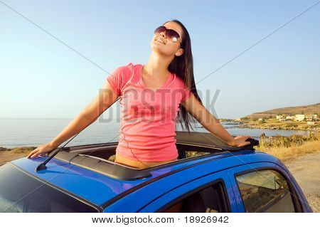 Beautiful young woman enjoying the sunset at the seaside