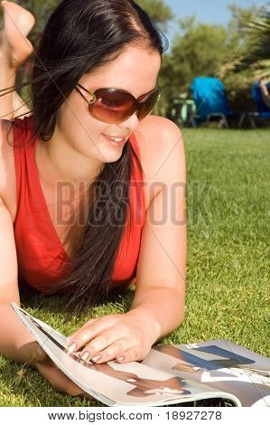 Beautiful young woman reading magazine in the park