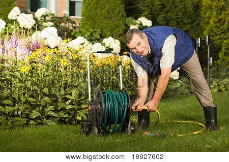 Senior man crimping hose in the garden