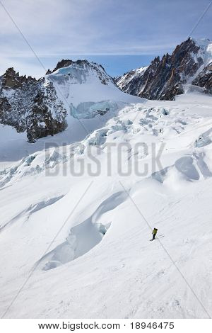 Male skier moving down in snow powder; envers du plan, valle blanche, Chamonix, Mont Blanc massif, France, Europe.