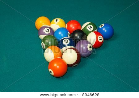 pool balls arranged on felt as triangle