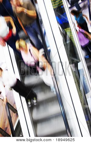 Shopping abstract. People rush on escalator motion blurred