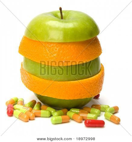 mixed sliced fruits and pills isolated on white background