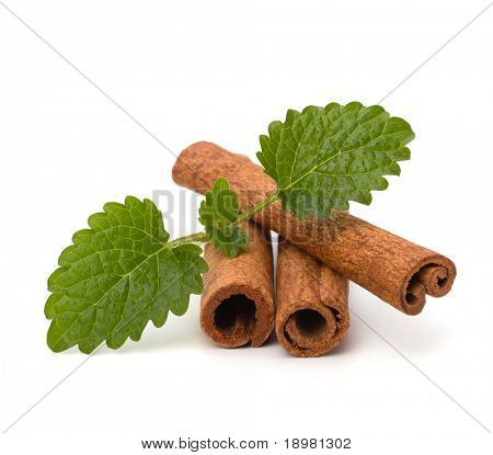 Cinnamon sticks and fresh bergamot mint leaf isolated on white background