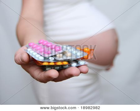 Pregnant woman holding medicine. Nine month. Third trimester