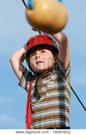 Portrait of young boy wearing helmet and climbing. Child in a wooden abstacle course in adventure playground