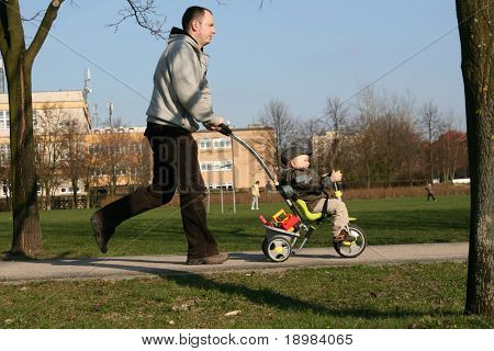 A young active family walking, running and playing at a park. Father is pushing tricycle.