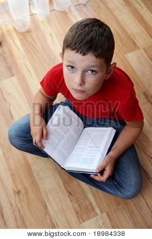 School boy sitting and reading book.