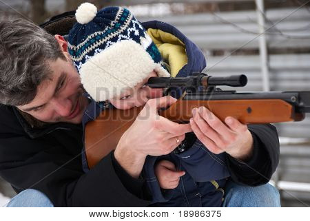 man and little boy aiming a rifle to shot
