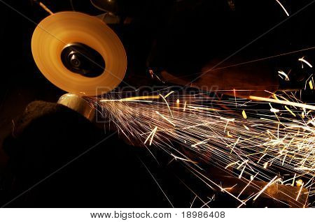 Manual sharpening and cutting of metal by abrasive disk machine