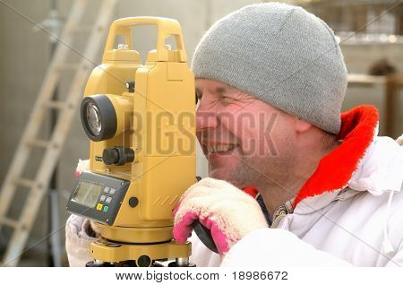 Land surveyor working with theodolite at a construction site
