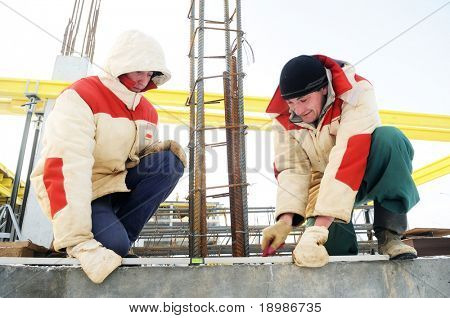 two workers at building area in winter using construction equipment - levelling instrument