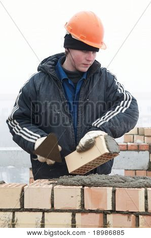 A brick layer worker building a brick wall at construction site