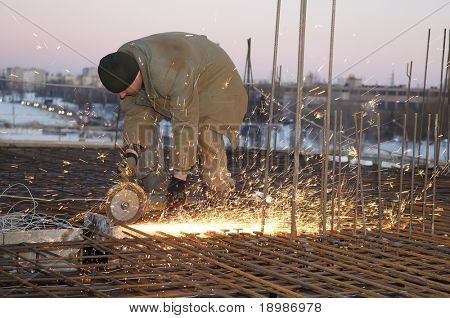 worker in cutting metal reinforcing lattice with abrasive cutoff saw disk