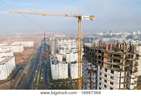 tower crane hoisting concrete blocks load on the top of building under construction