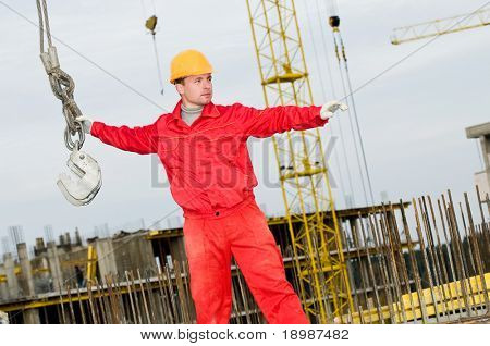 rigger builder in uniform and helmet operating with straps at construction area