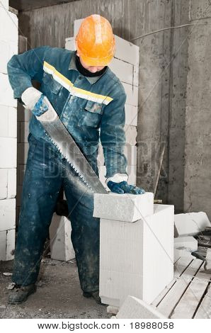 construction mason worker bricklayer sawing off a lime sand brick