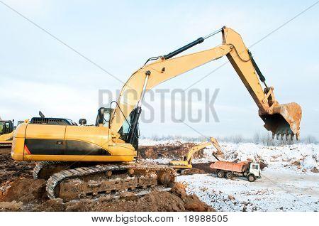 Heavy excavator loader at winter frozen soil moving works in sandpit