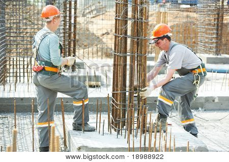 builder workers knitting metal rods bars into framework reinforcement for concrete pouring at construction site