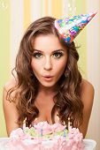 image of blow-up  - bautiful caucasian girl blowing candles on her cake - JPG