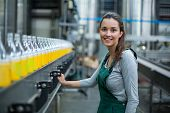 Portrait of female factory worker standing near production line at drinks production factory poster