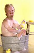 picture of midget  - tiny man takes a bath in a bucket of soapy water with a rubber ducky - JPG