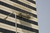 image of pressure-wash  - Two window washers washing building with pressure washer - JPG