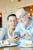 Affectionate seniors with smartphone searching in the net poster
