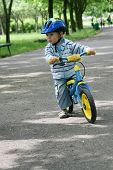 stock photo of happy baby boy  - 19 months old baby boy riding on his first bike in a helmet - JPG