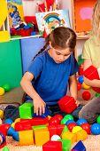 Children building blocks in kindergarten. Group kids playing toy on floor. Top view of interior pres poster