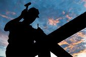 worker silhouette with hammer at roofing works over scenic dawn or sunset