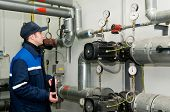 image of pressure vessel  - maintenance engineer checking technical data of heating system equipment in a boiler room - JPG