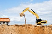 stock photo of open-pit mine  - Loader Excavator loading body of a dump truck tipper at open cast over blue sky in summer - JPG