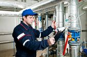 stock photo of pressure vessel  - maintenance engineer checking technical data of heating system equipment in a boiler room - JPG