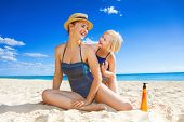 Smiling Young Mother And Child On Seashore Applying Spf poster