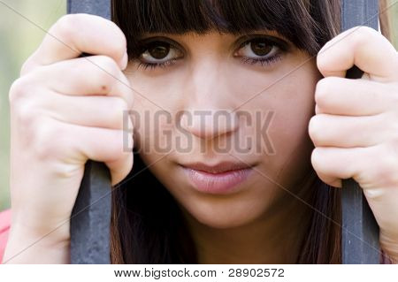 Young woman portrait in jail.