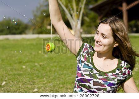 Young woman playing yo-yo in the park