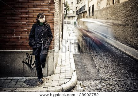 Woman on wall in urban background.