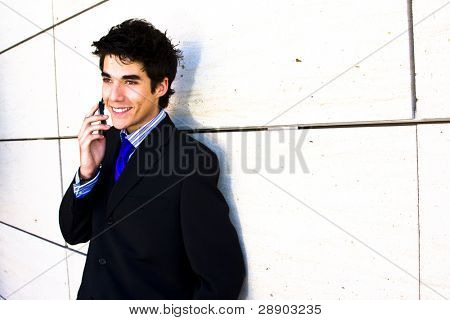 Smiling businessman at phone over white wall