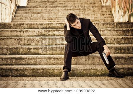 Young armed man waiting on the steps