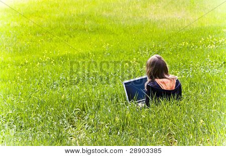 Blonde woman connected to internet in a meadow