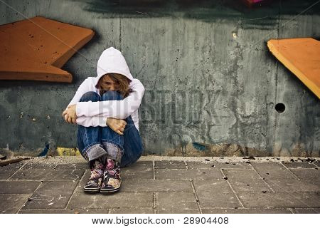 Suffering young woman on urban scenery.