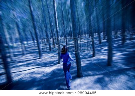 Woman escaping from unrevealed danger through the woods in the night