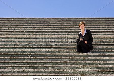Young blond businesswoman sited on steps