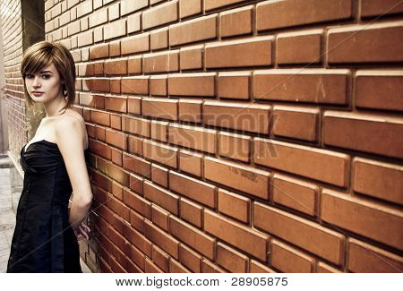 Beautiful blond woman on brick wall