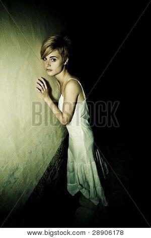 junge blonde Frau allein in der Dunkelheit